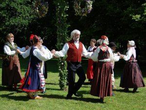 Ihmiset tanssimassa erilaisissa kansallispuvuissa